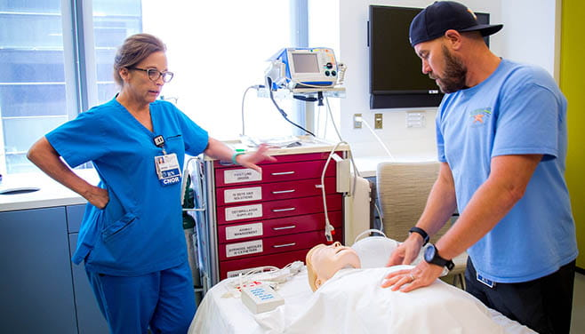 A female nurse supervises a male trainee practicing hands-on technique on a simulation mannequin.