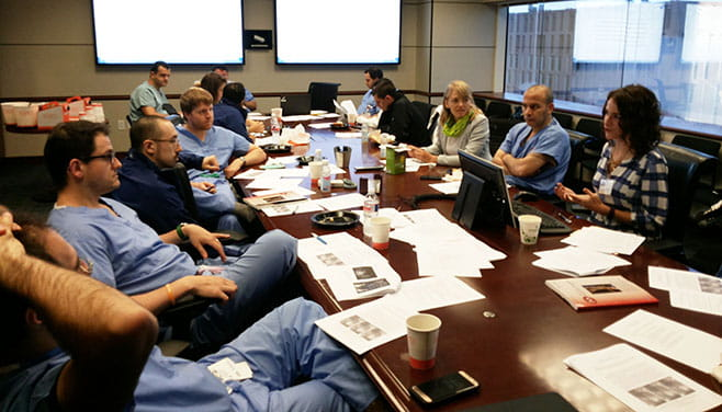 A group of cardiovascular fellows and an instructor sit around a table editing their manuscripts as a group.