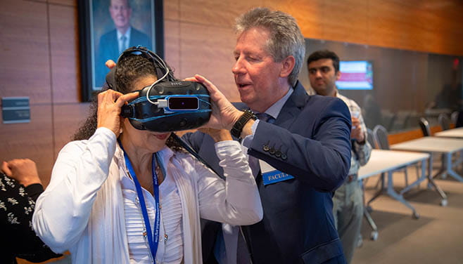 A man in a suit helps a woman adjust virtual reality goggles.