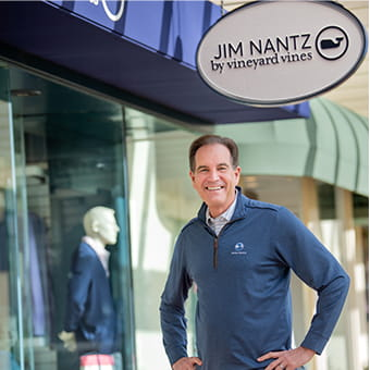 Jim Nantz standing in front of vineyard vines storefront