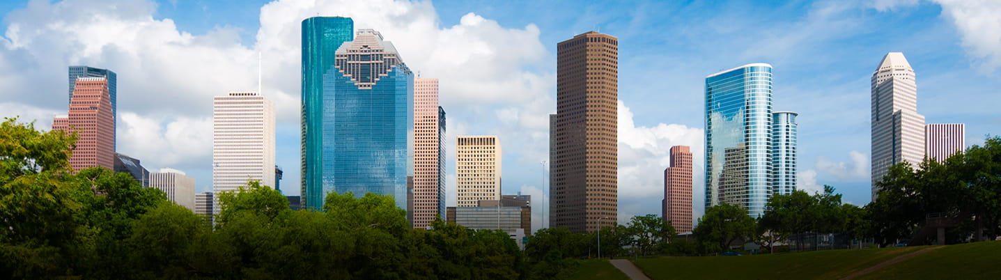 Downtown Houston skyline with tall buildings, blue sky and fluffy clouds