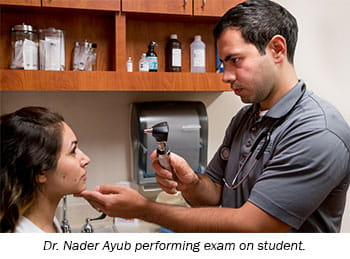 Dr. Nader Ayub performing exam on student