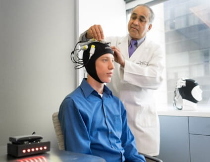 Dr Helekar placing magnetic stimulation device on patients head