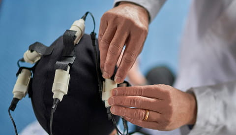 doctors hands adjusting electromagnetic cap