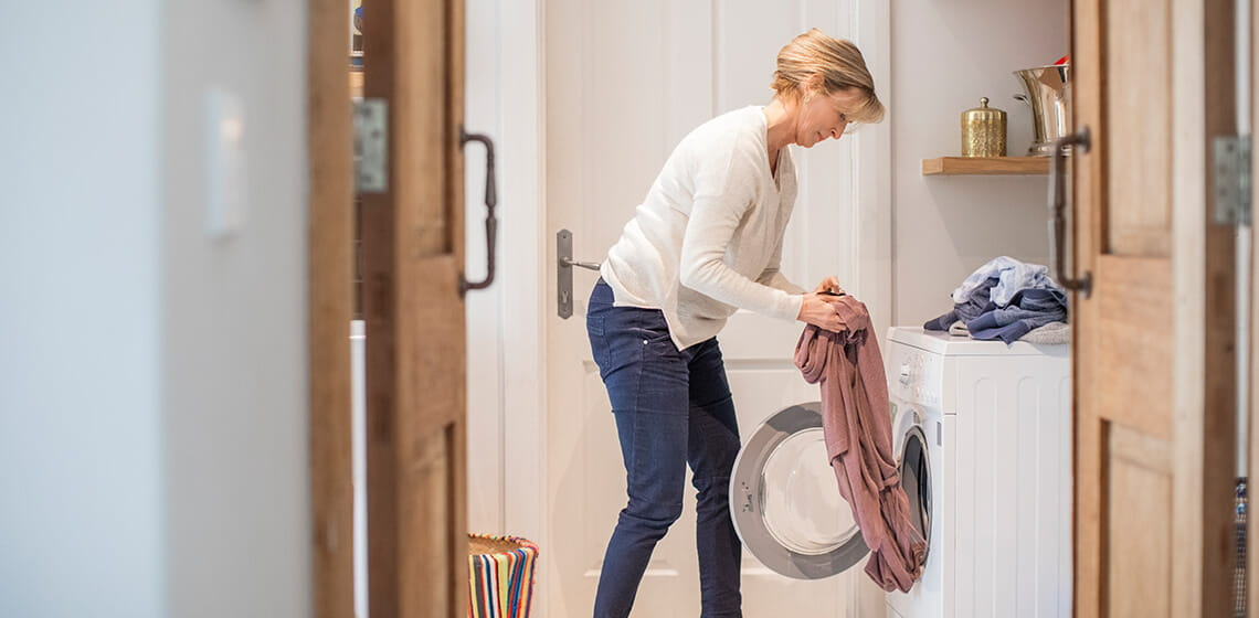 woman doing laundry bending at hip