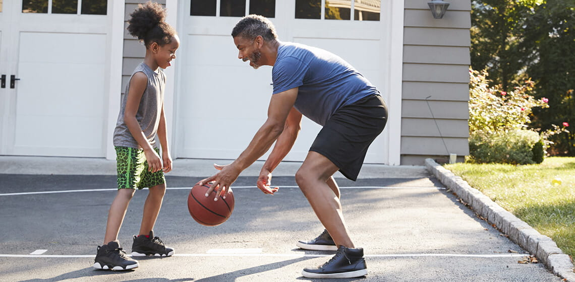 father and daughter playing basket ball bending knees