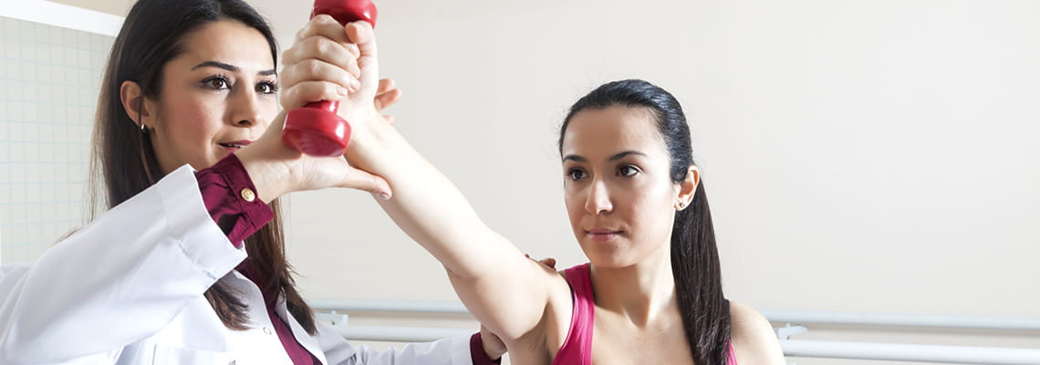 Houston Methodist Rehabilitation Associates physical therapist with patient lifting hand weight with right arm